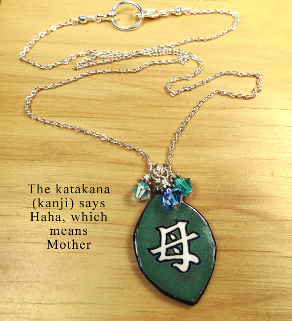 lacquered paper green necklace with the japanese kanji that says Mother