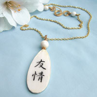 white and black lacquered paper necklace with the Japanese kanji that says Friendship