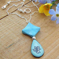 Lacquered paper turquoise teardrop pendant with aqua howlite and sterling silver. The Japanese kanji pendant says Mother.
