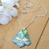 vintage peridot glass jewel and art deco style lacquered paper pendant on a silver plated chain