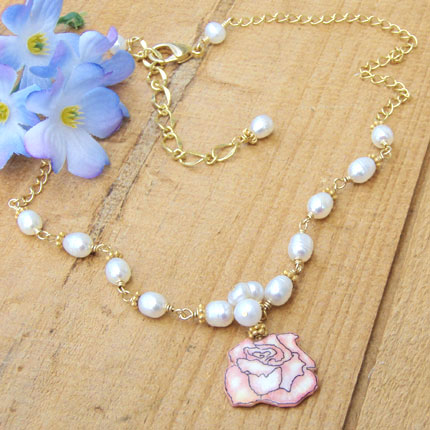 lacquered paper pink rose pendant paired with a cluster of small white pearls and handlinked pearls on a golden chain