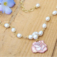 laquered paper pink rose pendant and white freshwater pearl cluster on a golden chain necklace