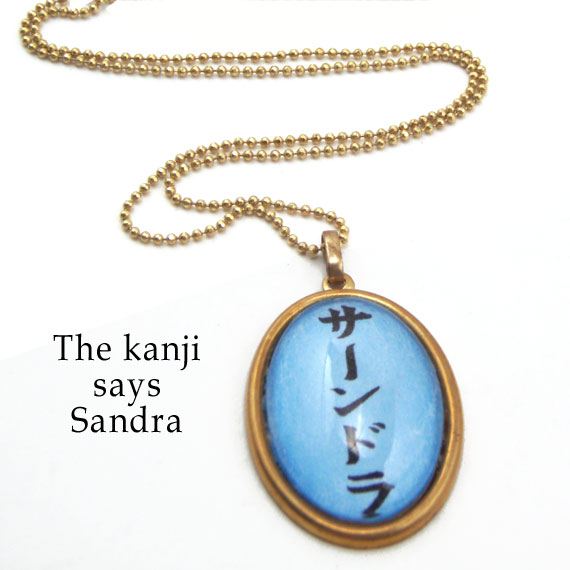 personalized kanji necklace that says Sandra in Japanese kanji...oval pendant is shown in blue with black
